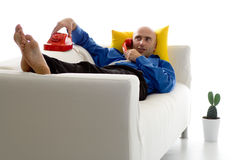 Man On Couch With Phone. Man in casual business clothes relaxing on a white couch against a yellow pillow.  He is holding a red phone onto the back of the couch Stock Photography