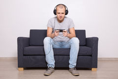 Man on couch playing games or watching movie on mobile phone Stock Photo