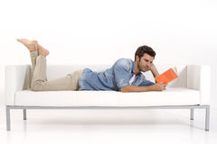 Man on the couch reading a book Stock Photo