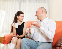 Man on  couch and talking with  woman Royalty Free Stock Photography