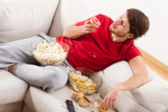 Man on couch with treats Stock Photo