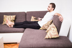 Man on the couch watching tv, changing channels at sofa Royalty Free Stock Photography