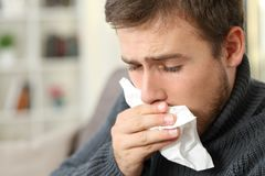 Man coughing covering mouth with a tissue at home. Man coughing covering mouth with a tissue sitting on a couch in a house interior Stock Photo