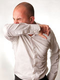 Man Coughing into Elbow. A man coughing/sneezing into elbow/arm to not spread germs Stock Images