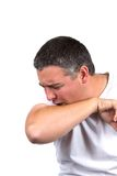 Man Coughing Inside Elbow. Sick adult male coughs inside his elbow to prevent the spread of germs Stock Photos