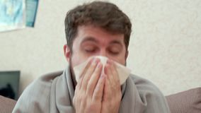 Man coughing into a paper handkerchief. He has a cold, headache, fever, chills. Sitting on the couch, wrapped in a blanket stock footage