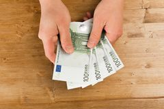 Man count euro on wooden table.  stock photo