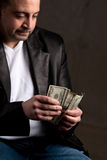 Man Counting Cash. A shady looking man counting a handful of one hundred dollar bills. Shallow depth of field with focus on the money Stock Photos