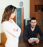 Man counting cash, woman watching him Stock Image