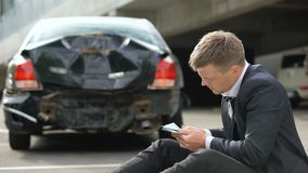 Man counting dollars, looking at damage car after accident, repairs cost. Stock footage stock footage