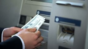 Man counting dollars withdrawn from ATM, 24h service, easy banking operation. Stock photo royalty free stock photography