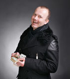 Man counting money. Young handsome man in winter coat counting money on a  gray background Stock Photography