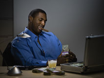 Man counting money at desk. Business man counting money at desk with cigar and gun Royalty Free Stock Photos