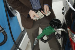 Man Counting Money At Fuel Station Royalty Free Stock Image