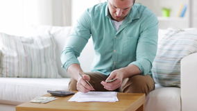 Man counting money and making notes at home stock video footage