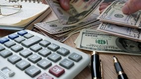Dollar bills and calculator. Savings and home budget. Man counting money on an office desk. Dollar bills and calculator. Savings and home budget stock footage