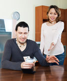 Man counting money, wife watching him Stock Photo
