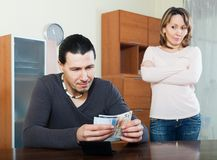 Man counting money, wife watching Stock Photo