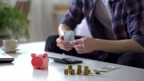 Man counting month salary, hiding money from wife into piggy bank, earnings. Stock photo royalty free stock image