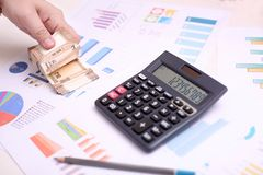 Man is counting new Indian 10 rupee currency. Picture of calculator, chart paper and pencil royalty free stock image