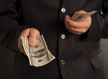 Man counting your money. On a black background stock photography