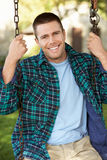 Man on country garden swing. Smiling at camera Stock Photography