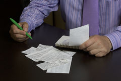 The man counts the cost of cash Cheques. A family budget. Stock Images