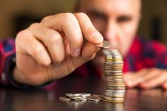 Man counts his coins on a table Stock Photo
