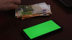 Euro bills, counting money, near the phone with a chromakey