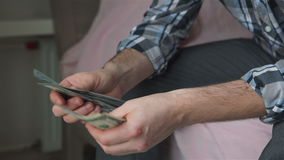 Man counts the money. And plans to purchase stock footage