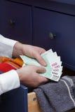Man counts money for rainy day Stock Photo