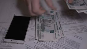 The man counts money Russian ruble over white table for Utility bills pay slow motion hd footage. The man counts money Russian ruble close-up over white table stock footage