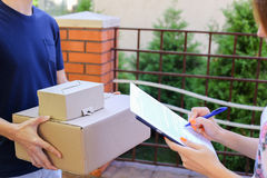 Man Courier Brings Order to Customer, Gives Pen and Paper to Sig royalty free stock photo