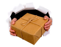 Man or courier hands delivering or giving parcel through torn white paper background Royalty Free Stock Photo