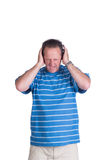 Man coveing ears in pain. Middle aged white man in a blue striped shirt holding his hands over his ears while he is screaming in frustration or anger and pain Royalty Free Stock Photography