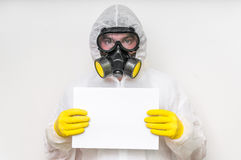 Man in coveralls with gas mask is holding blank white paper. Ecology and pollution concept stock image