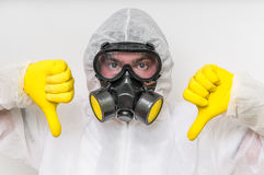 Man in coveralls with gas mask is showing negative gesture. Ecology and pollution concept stock photos