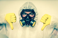 Man in coveralls with gas mask is showing negative gesture. Retro style stock images