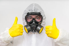 Man in coveralls with gas mask is showing positive gesture. Ecology and pollution concept stock photo