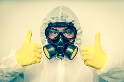 Man in coveralls with gas mask is showing positive gesture. Retro style royalty free stock images