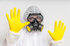 Man in coveralls with gas mask is showing stop gesture. Ecology and pollution concept royalty free stock photo