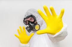 Man in coveralls with gas mask is showing stop gesture. Ecology and pollution concept stock photography