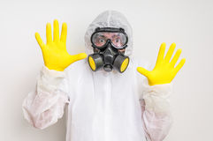 Man in coveralls with gas mask is showing stop gesture. Ecology and pollution concept stock images