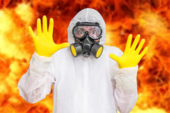 Man in coveralls with gas mask is showing stop gesture. Nuclear and biohazard concept stock image