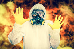 Man in coveralls with gas mask is showing stop gesture. Nuclear and biohazard concept - retro style royalty free stock photos