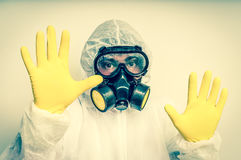 Man in coveralls with gas mask is showing stop gesture. Retro style stock photos