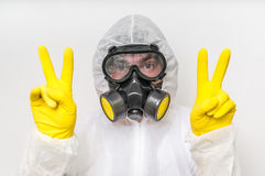 Man in coveralls with gas mask is showing victory symbol. Ecology and pollution concept royalty free stock photography