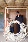 Man in coveralls and young boy holding electrical cables Royalty Free Stock Photo