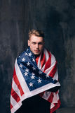 Man is covered by american flag on dark background. Patriot, national event celebration, pride, usa citizen concept Stock Images