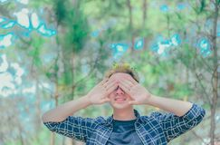 Man Covered Eyes by His Hand Standing on Surrounded Trees Stock Photos
